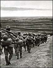 "Japanese troops on the way to ""wipe out Chungking guerillas."" A photo used for a military postcard."
