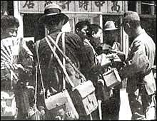 Japanese troops and Chinese street vendors in Nanking.